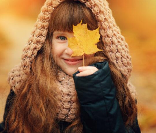 little girl hides eye with autumn leaf